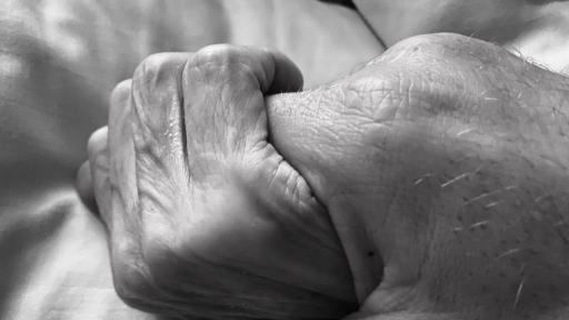 Zwei Hände verschließen sich ineinander.