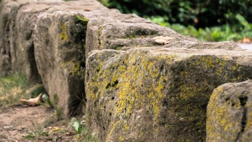 Mehrere große, quadratische, verwitterte Natursteine liegen hintereinander.