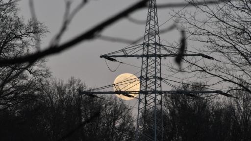 Hinter einem Strommast scheint hell der Mond.