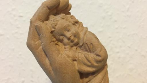 Eine sehr große, schützende Hand, in der sich ein Kind ausruht.