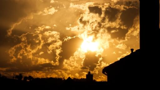 Eine untergehende Sonne zwischen Wolken über Häuser