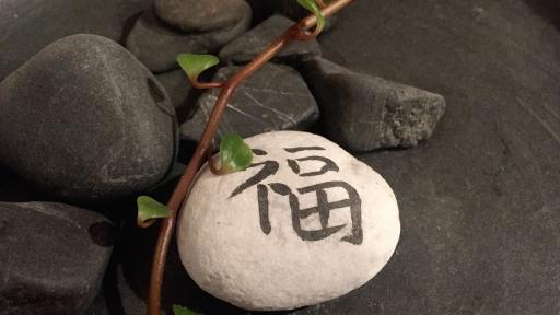 Mehrere schwarze Steine. Ein Stein ist weiß und mit einem chinesischen Schriftzeichen versehen
