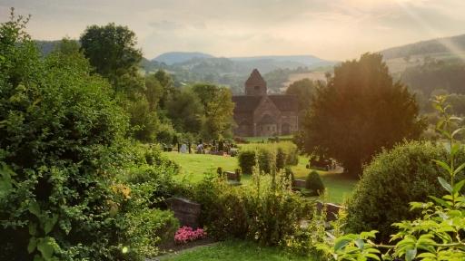 Eine alte Kirche auf einem Friedhof im Hintergrund grüne Hügel