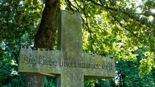 Ein Kreuz aus Stein, darauf der Text: Die Liebe höret nimmer auf!