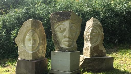 Drei Steinquader stehen nebeneinander auf einer Wiese. In die Steine sind Gesichter gemeißelt worden.