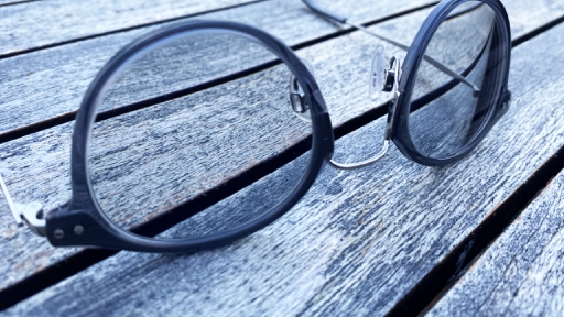 Eine Brille liegt auf einem Holztisch.
