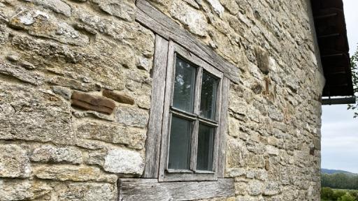 Eine aus Natursteinen gemauerte Wand, darin ein altes Sprossenfenster mit Holzrahmen.