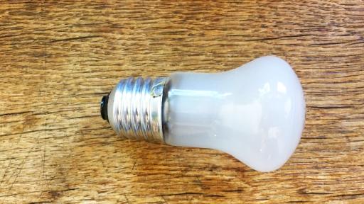 Eine Glühbirne liegt auf einer alten Holzplatte.