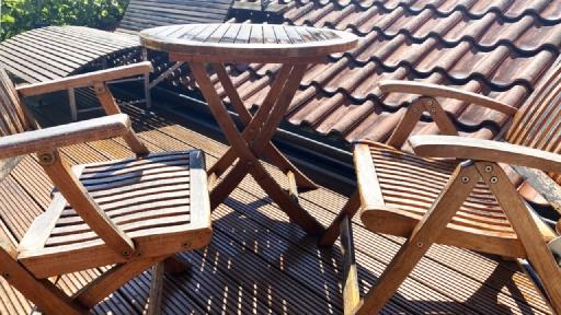 Zwei Gartenstühle auf einem Balkon stehen sich gegenüber.
