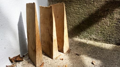 Drei Holzkeile aufrecht nebeneinander gestellt.
