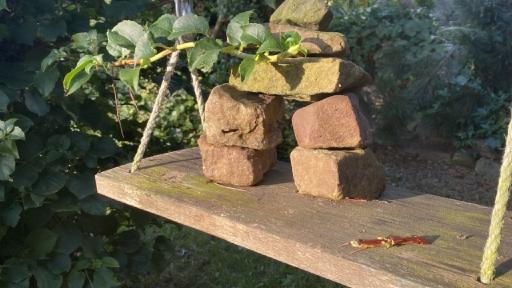 Ein kleiner Turm aus Steinen auf dem Sitzbrett einer Schaukel.