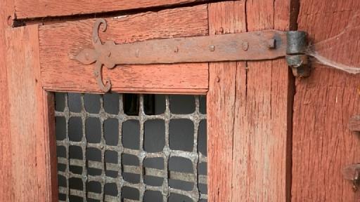 Eine alte Tür mit einem Gitter vor der Fensteröffnung.