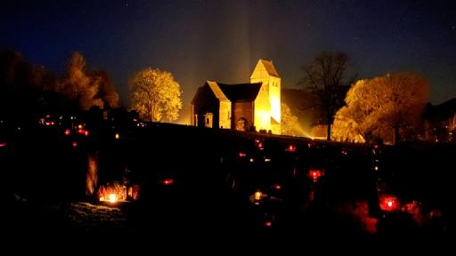 Nachts. Viele brennende Kerzen auf dem Friedhof in Lügde. Im Hintergrund die Kilianskirche. Sie wird von Strahlern erhellt.