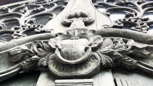 Mit viel Schnitzereien verzierter Torbogen eines alten Fachwerkhauses.