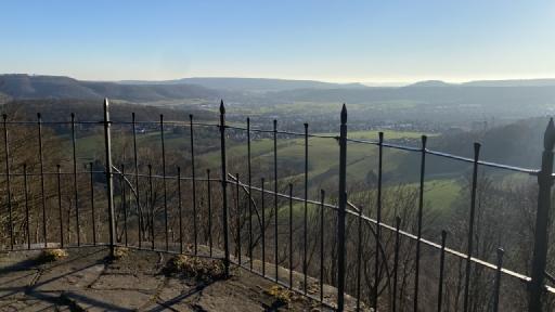 Geländer im Vordergrund, im Hintergrund zwei Städte umrahmt von Bergen.