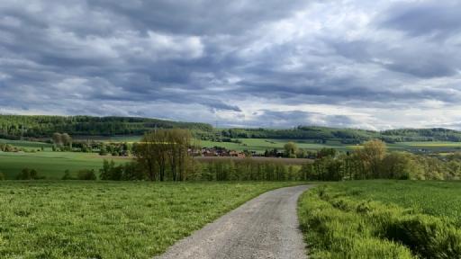 Blick auf ein Dorf. Im Vordergrund ein Weg, links und rechts Felder, hinter dem Dorf Felder und eine Berg mit Wald. Am Himmel viele dunkle Wolken.