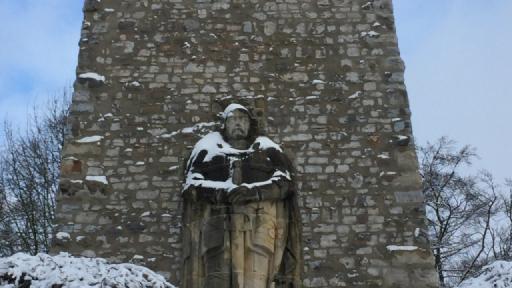 Eine Steinstatue von Bismarck auf der Schnee liegt.