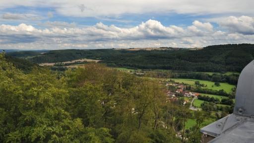 Blick von einem Turm in ein Tal mit einer Straßen an der noch vereinzelnd Gebäude stehen.