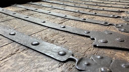 Deckel einer alten Holzkiste mit schweren Eisenbeschlägen.