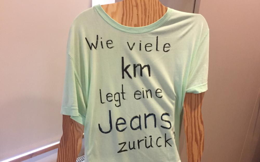 Ein T-Shirt mit der Aufschrift: Wie viele Kilometer legt eine Jeans zurück?