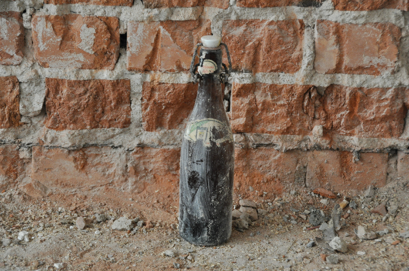Eine alte Bügelflasche vor Ziegelsteinen