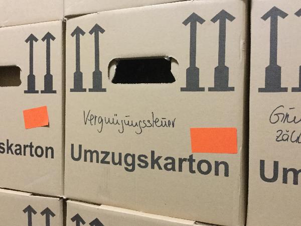 Umzugskartons. Ein Karton trägt die Aufschrift Vergnügungssteuer