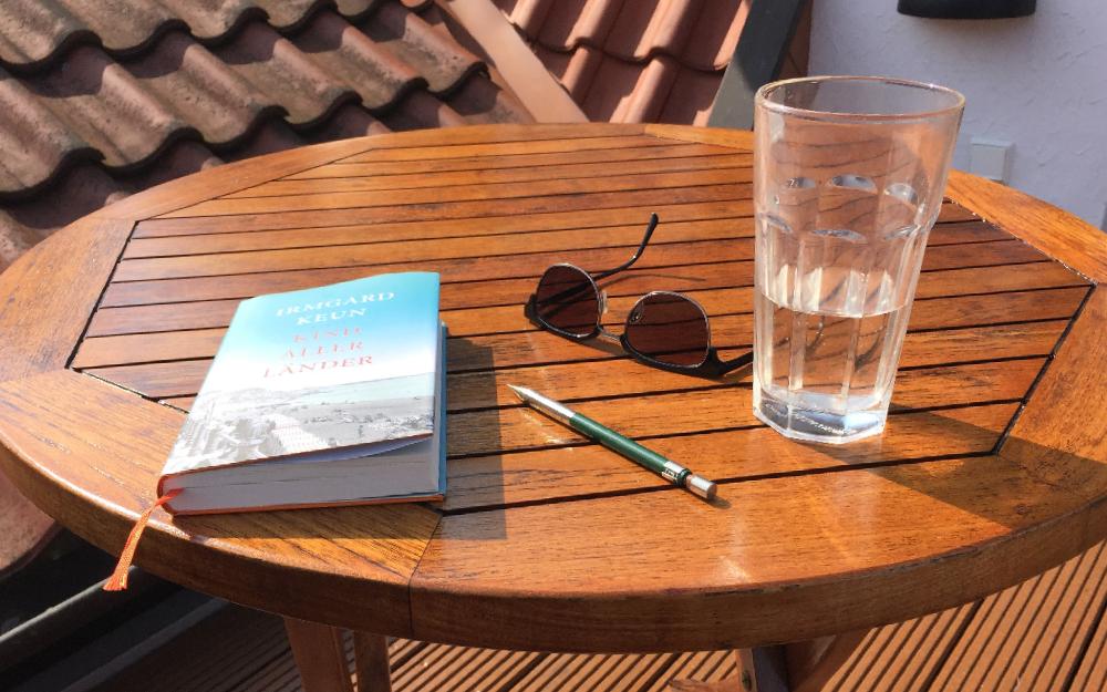 Ein Tisch auf dem Balkon. Auf dem Tisch liegt ein Buch, eine Brille und es steht ein Glas Wasser darauf
