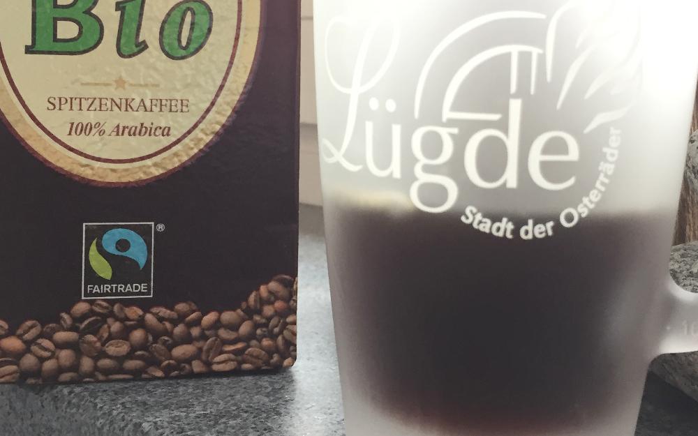 Eine Kaffeepackung mit dem Fairtrade-Logo und eine Kaffeetasse mit dem Schriftzug Lügde, Stadt der Osterräder
