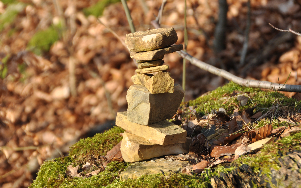 Ein aus kleinen Steinen gebautes Türmchen auf einem Baumstumpf
