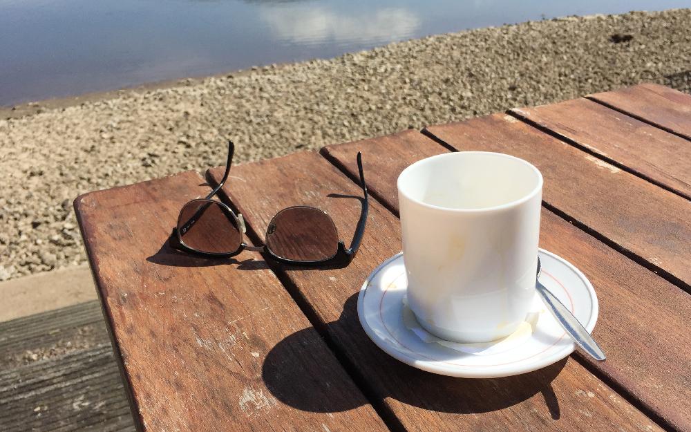 Eine Brille und eine Tasse auf einem Holztisch