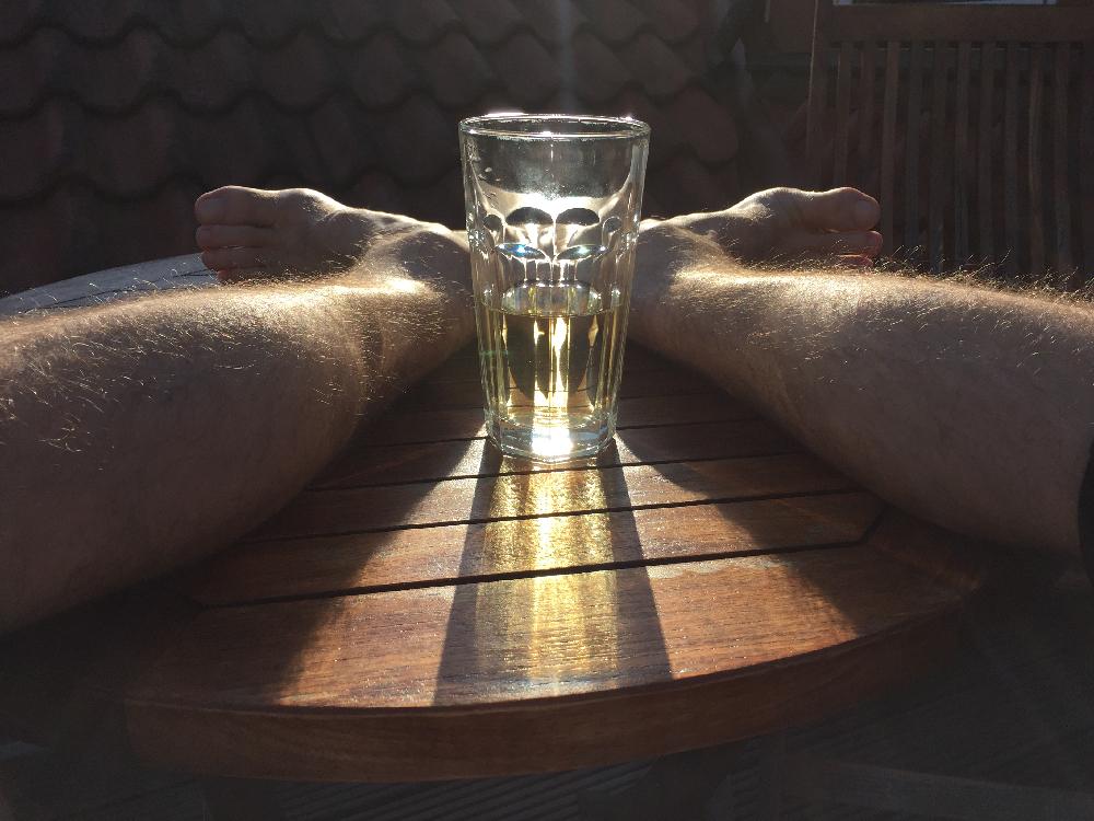Beine, Füße und ein Glas Apfelschorle