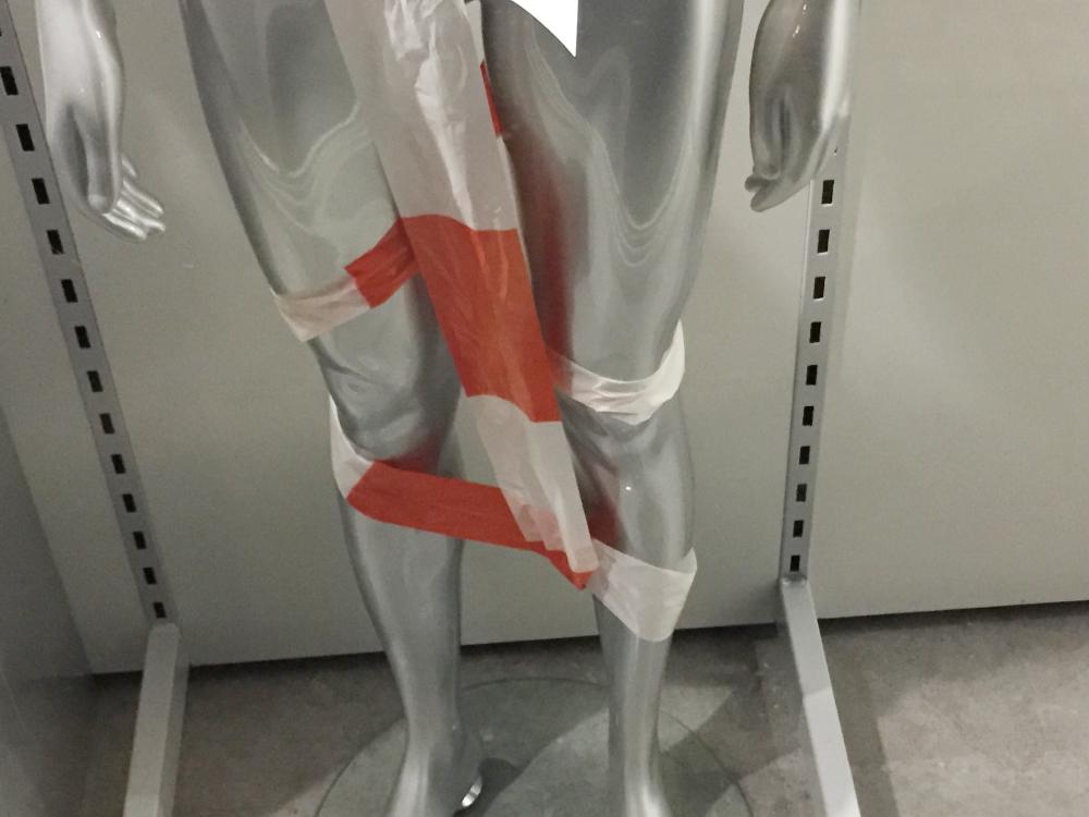 Eine Schaufensterpuppe mit Absperrband
