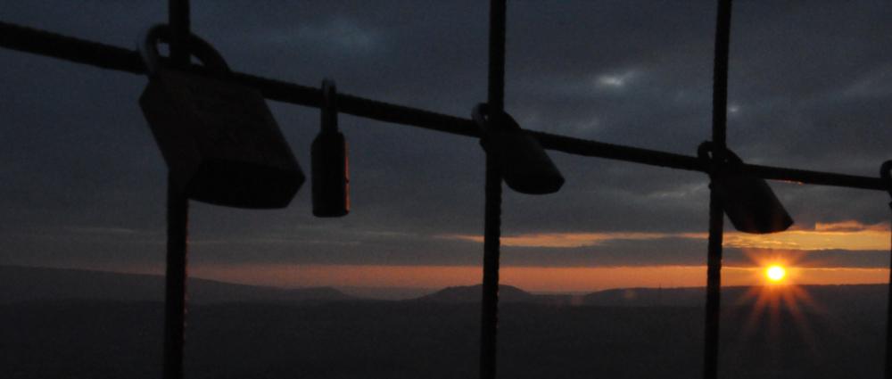 Liebesschlösser am Spelunkenturm in Bad Pyrmont, im Hintergrund ein Sonnenuntergang