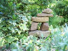 Efeu, darin ein Gebilde aus Steinen