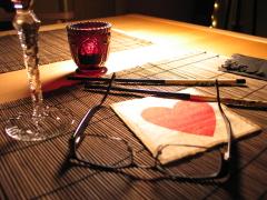 Ein Stillleben mit Platzdecke, Essstäbchen, Brille, Weinglas