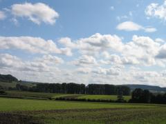 Im Vordergrund ein Acker, im Hintergrund Hügel, darüber viele Wolken