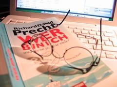 Ein aufgeschlagenes Buch liegt auf einer Computer-Tastatur, darauf liegt auch eine Brille.