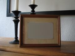 Ein Bilderrahmen vor zwei Kerzenständer, in dem Rahmen fehlt das Bild.