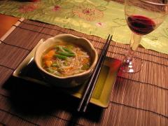 Ein Schälchen mit Suppe, daneben Stäbchen und ein Glas mit Rotwein