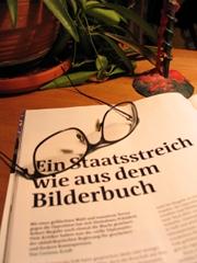 Eine Brille liegt auf einem Heft; der Titel auf dem Heft: Ein Staatsstreich wie aus dem Bilderbuch