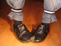 Eine Hose, der Schlag ist unterhalb der Waden mit Hosenbändern umgeschlagen und befestigt