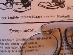 Der Seitenausschnitt eines Buches, darauf liegt eine Brille