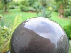 Im Vordergrund eine Metallkugel im Hintergrund ein Garten