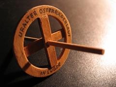 Eine Miniatur des Osterrades, ein hölzernes Rad mit vier Speichen und einer Querstange