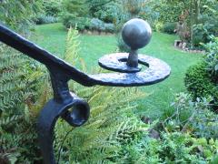 Ein Treppengeländer aus Metall, im Hintergrund ein Garten