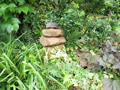 Ein kleiner Turm aus Steinen inmitten von vielen Pflanzen