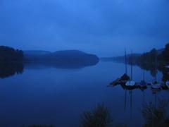 In einem See spiegeln sich die umliegenden Berge, im See liegen kleine Segelboote vor Anker.