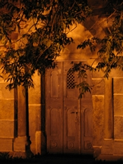Eine kleine Kirchentür bei nächtlicher Beleuchtung, davor die Zweige eines Baumes.