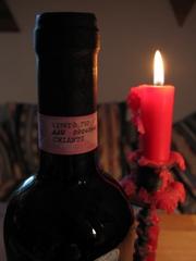 Der Flaschenhals einer Weinflasche, daneben eine brennende Kerze auf einem Kerzenständer.