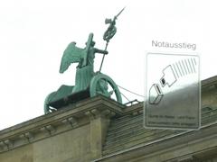 Rückseite des Brandenburger Tores mit der Quadriga, daneben ein Schild mit dem Text Notausgang